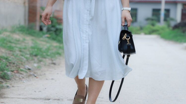 Hottest Bags for The Spring Woman in flowy skit carrying small black clutch bag
