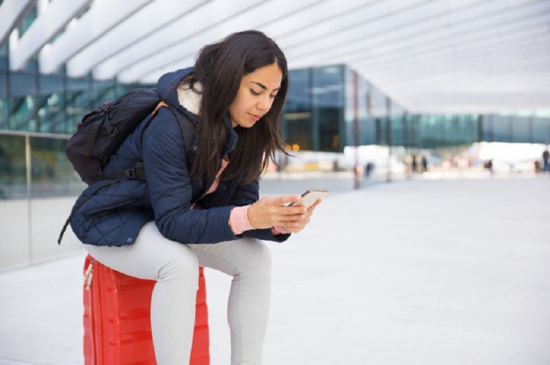 Woman sitting on Red Suitcase while on her smartphone