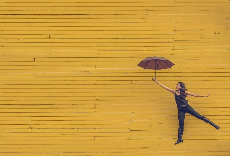 Woman with Umbrella Floating in Front of a Yellow Wall
