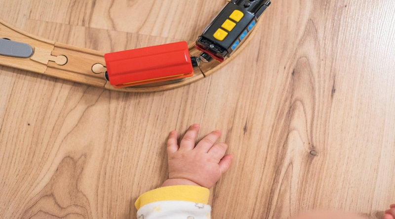 Make Your Home Safer for Kids Childs hand by toy train on train track