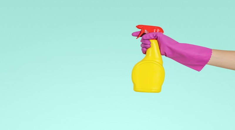 Hiring A Cleaning Company Gloved hand holding bright yellow spray bottled