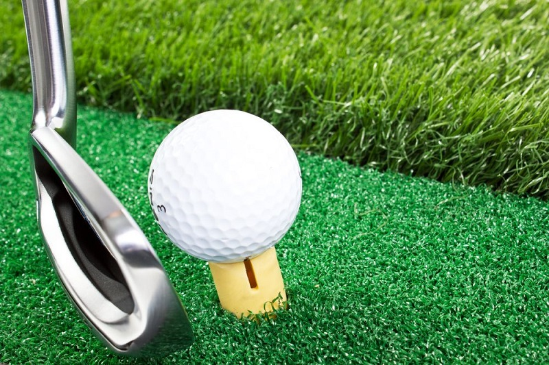 Artificial grass with ball on tee and putter Perfecting your putt at home
