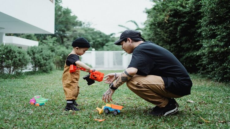 Get Your Garden Ready Man and Little Boy in Back Yard playing with toy trucks