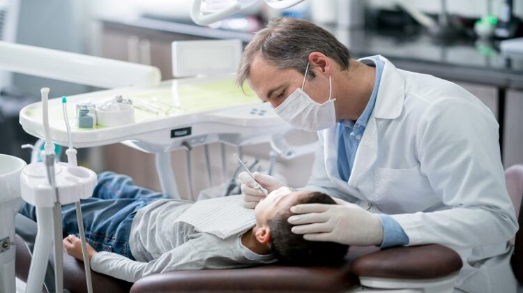Things Every Parent Should Know About Baby Teeth Pediatric dentist checking teeth on a boy
