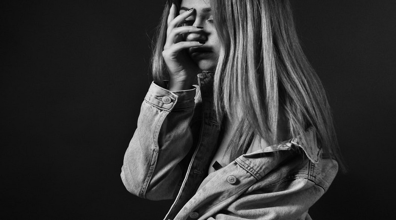 Help Your Teen Overcome a Loss Sad teenage girl with long hair wearing jean jacket