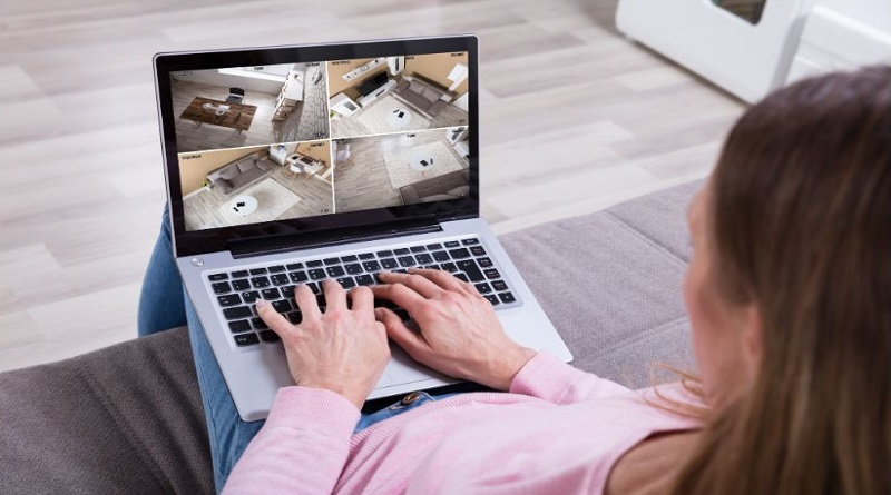 Woman monitoring her home security cameras via her laptop