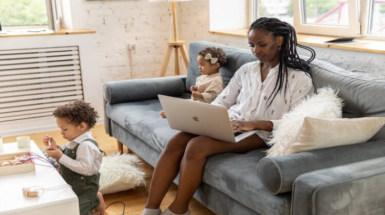 Home Office With A Family Woman sitting on sofa, working on laptop with her small children nearby
