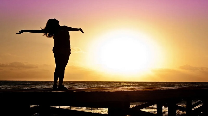 Change Your Life for the Better Woman standing on a pier at the beach at sunset