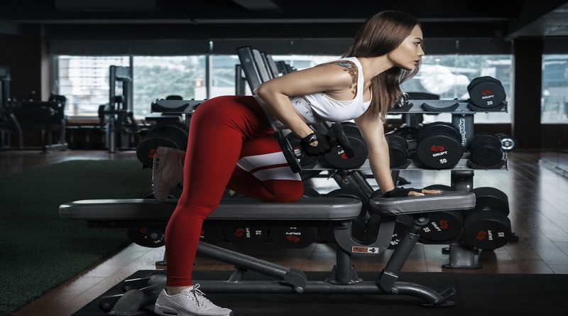 The Right Gym Wear Brunet working out in gym wearing bright red with white workout clothing