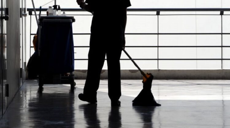Commercial Cleaning Brisbane Cleaner mopping floor with cleaning cart in background