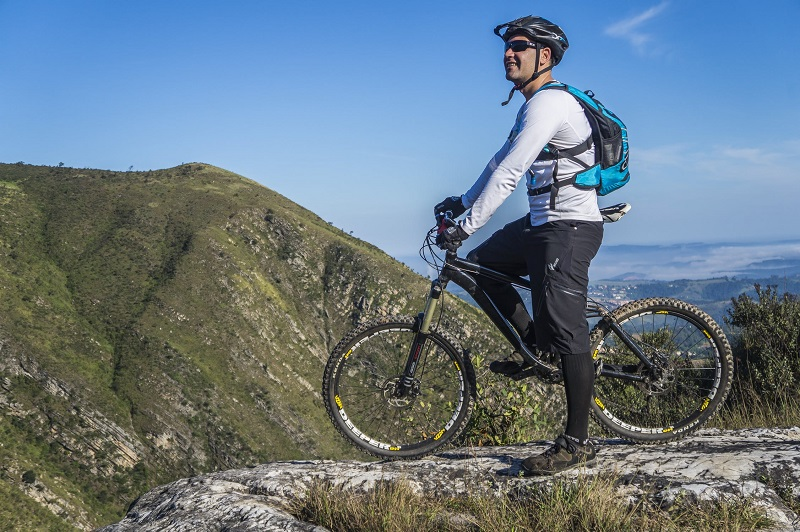 Cyclist on Mountain Bike wearing safety helpmet and wearing sunglasses