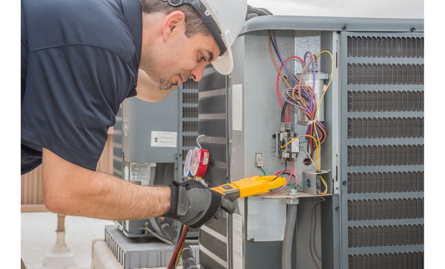 How to Find an HVAC Contractor HVAC repairman reading volt meter on HVAC Unit