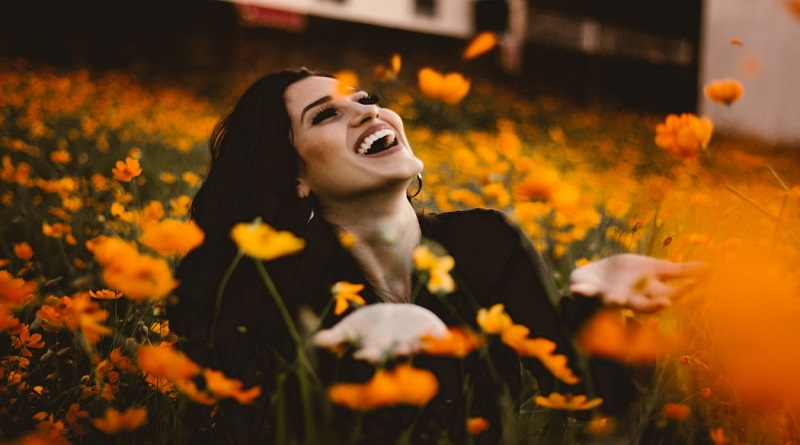 Happy smiling woman in a field of flowers