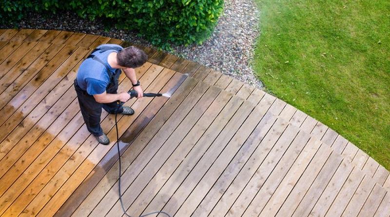 Pressure Washers Man pressuring washing a wood deck