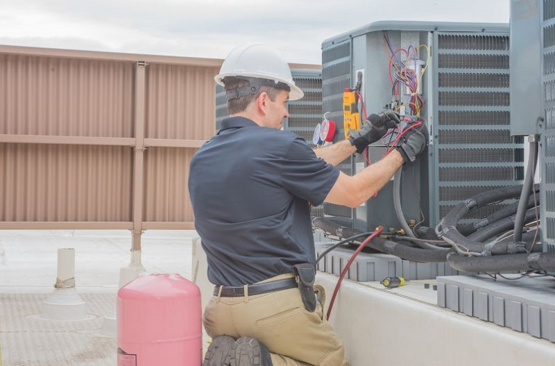 How to Find an HVAC Contractor HAVC expert testing condenser on HVAC unit