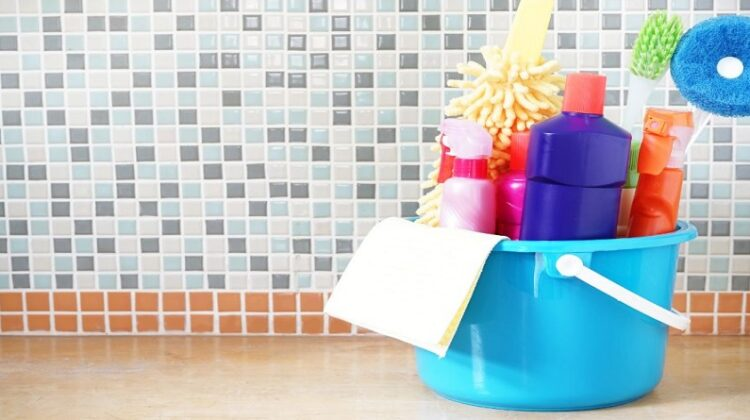 Best Disinfecting Practices Small blue bucket filled with cleaning supplies sitting on kitchen counter