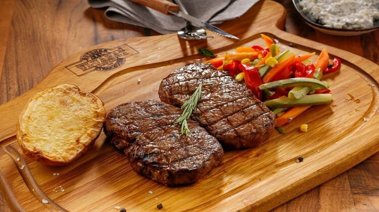 Steaks resting on wood platter with veggies and garlic toast Cook the Perfect Beef Steak