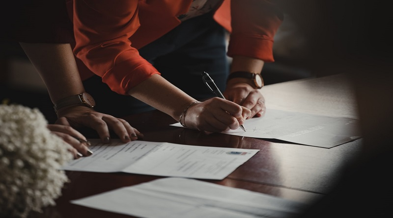 Two people with papers on desk signing with pen Insurance For Homes