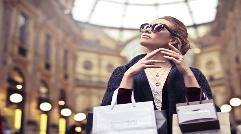 Woman wearing sunglasses and holding numerous shopping bags