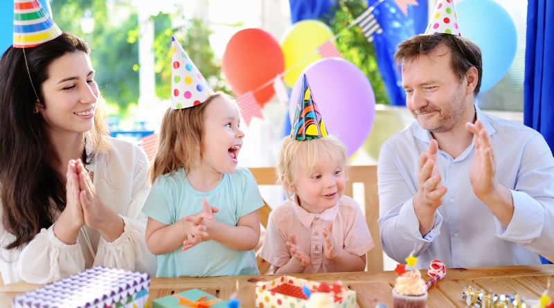 Adults and children wearing party hats at a birthday party