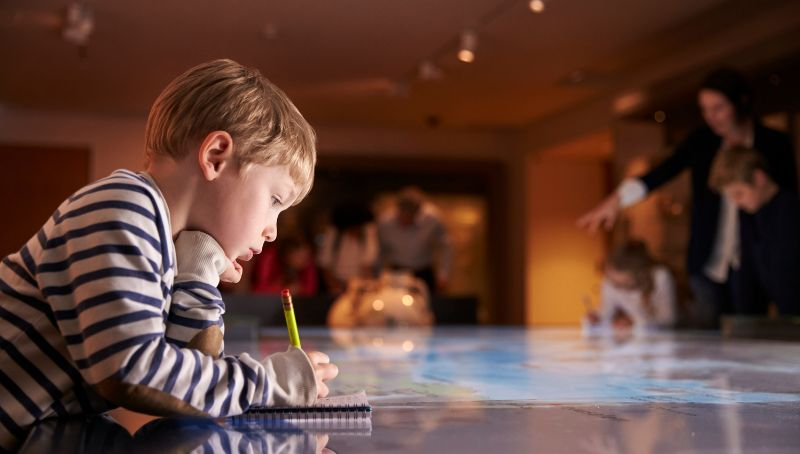 Little Boy taking Notes at a Museum Family fun that doesn't cost the world