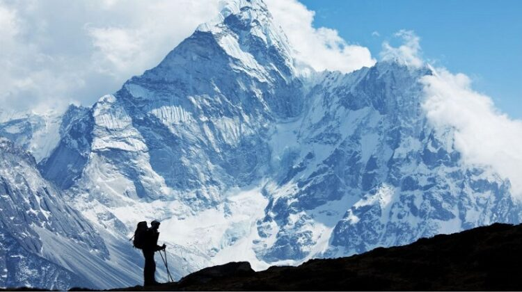 Unique Foreign Holiday Experiences Silhouette of man on skis looking up at Mount Everest
