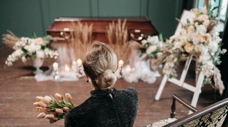 Plan an Amazing Funeral Woman holding flowers gazing at a casket at a funeral