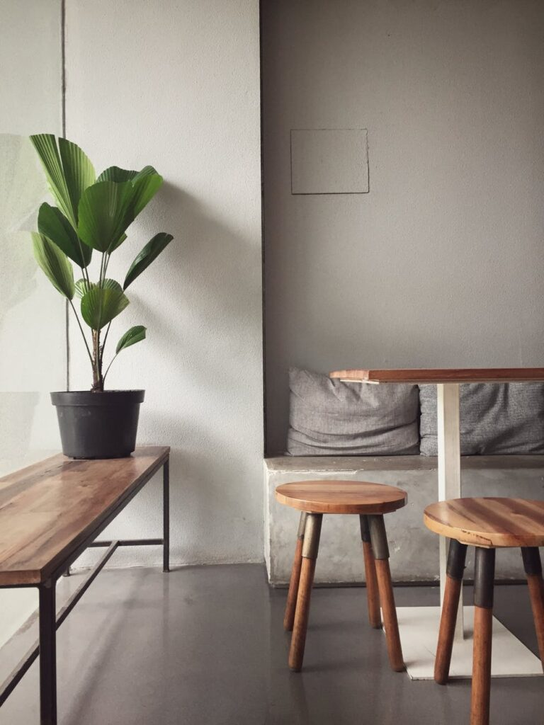 Airy room with wooden table, stools and bench with plant