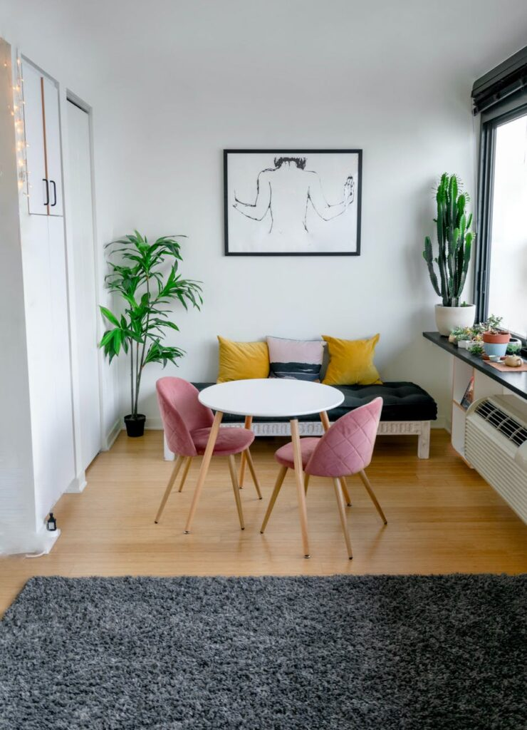 Contemporary room with table for two, futon and large window with ledge for plants