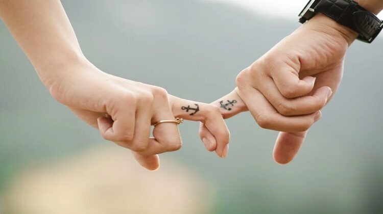 Getting Your First Tattoo Couple with matching anchor tattoos on their fingers