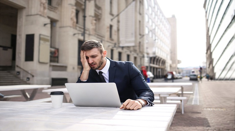 Hidden Health Hazards In Your Workplace Frustrated man at outdoor table looking at his laptop