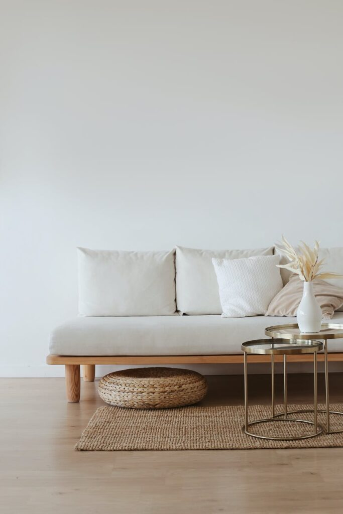 Bring The Natural World Indoors Minimal room with light wood floors, white sofa, and glass accent table