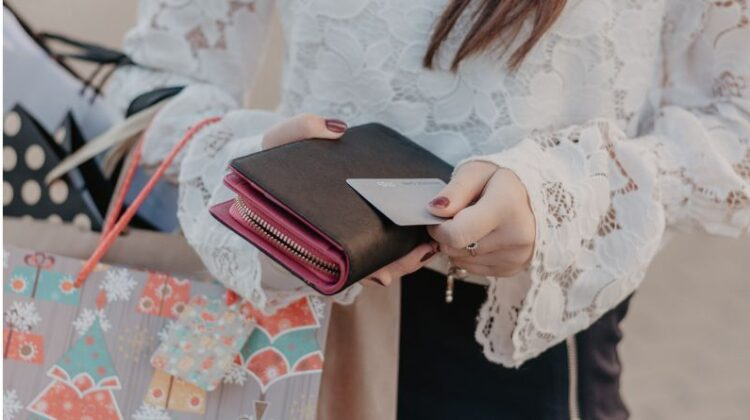 Upgrade Your Wardrobe By Adding A New Wallet Woman holding shopping bag and a wallet with credit card