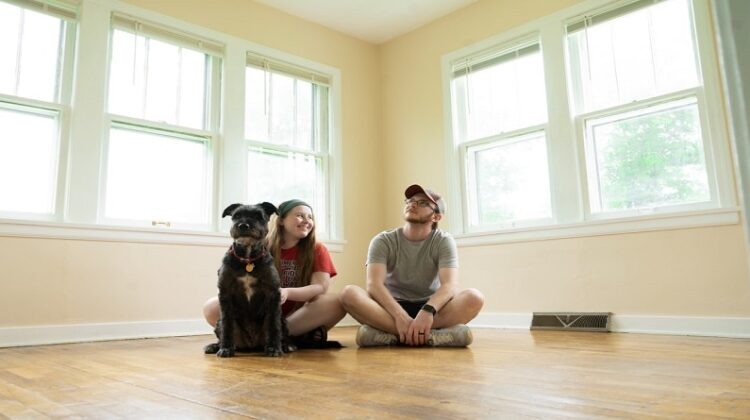 Up Sticks And Move Young couple and their dog sitting on the floor in a room with no furniture or drapes on the windows