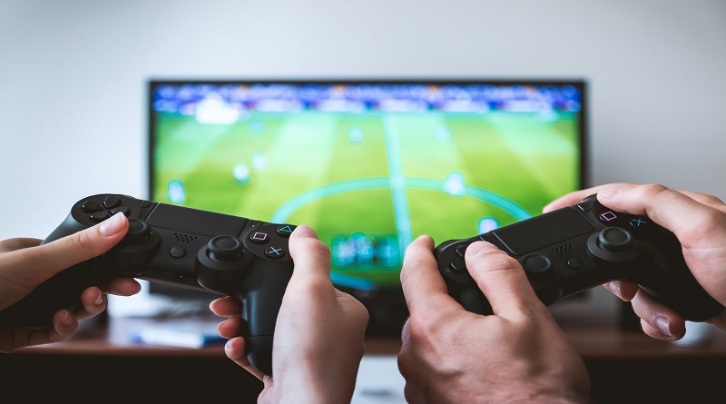 At-Home Activities For You and Your Partner Man and woman playing video games together on big screen TV