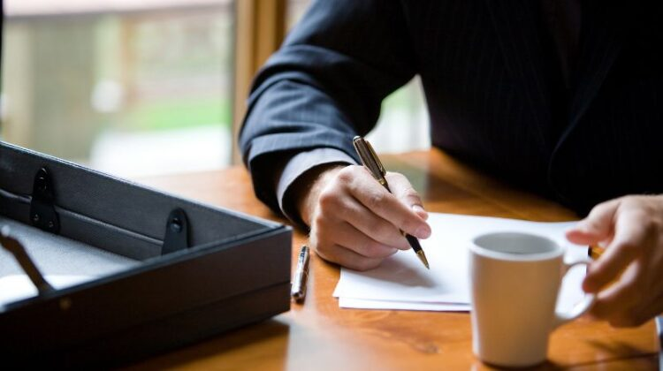 Man writing on a pad of paper Writing a Will