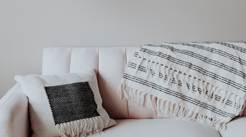 Thrift Shopping for Furniture Off white sofa with pillow and throw blanket