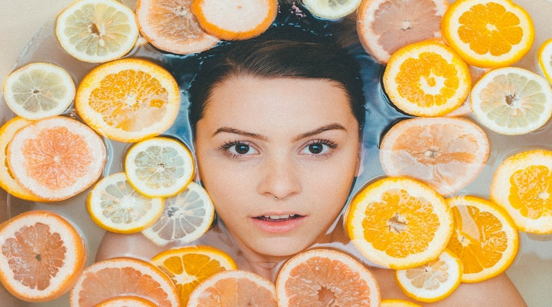 Skincare Hacks Woman floating in tub filled with sliced citrus fruit