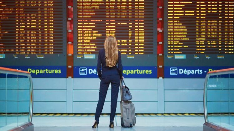 Ways to Dress Up Woman wearing a pantsuit and heels, with roller bag luggage at airport