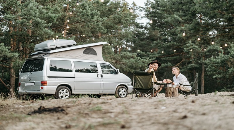 Gadgets You Need When Going Camping Man and woman sitting on camp chairs by their pop-up camper van