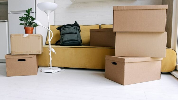 Getting Ready To Move Home Packing boxes in living room with yellow sofa and white floor lamp
