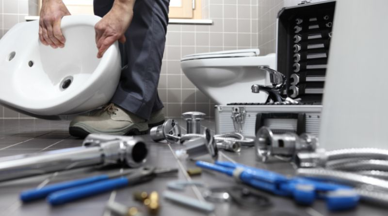 Plumber holding sink surrounded by tools and supplies on the floor around his feet