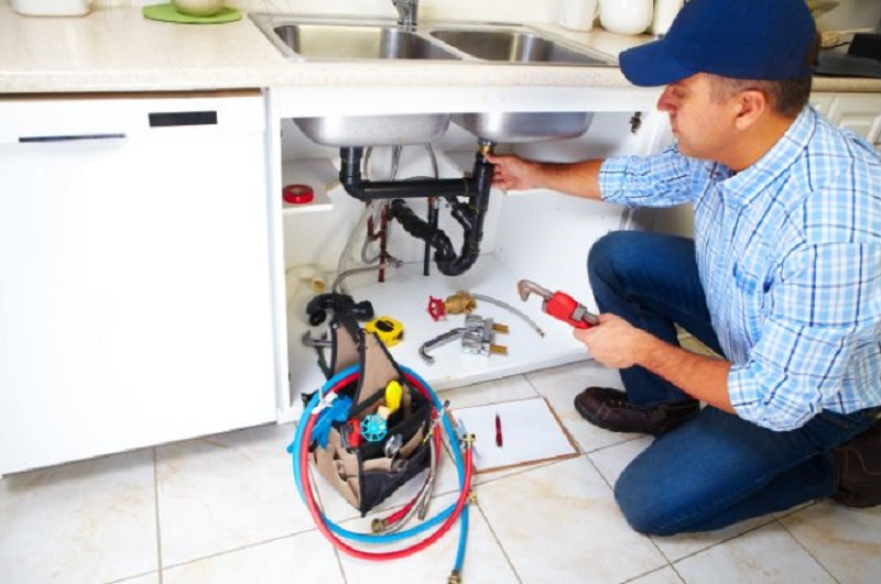 The Benefits of Plumbers Plumber working on Pipes under Kitchen Sink
