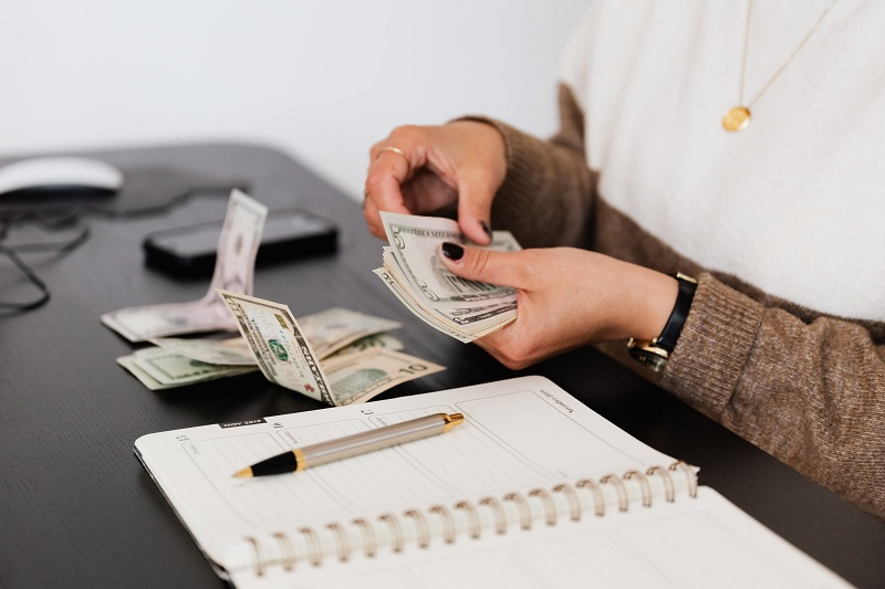 Woman counting money at her desk Improving Your Financial Situation