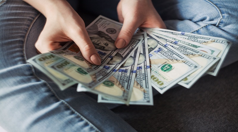 Woman in Jeans Holding lots of 100 Dollar Bills