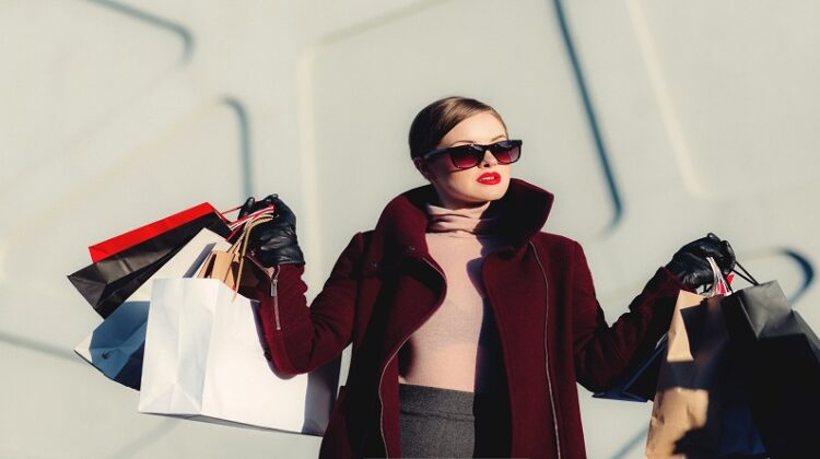 Woman in coat and sunglasses holding multiple shopping bags