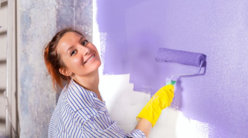 Add Value To Your Home Woman wearing yellow rubber gloves roller painting a wall purple