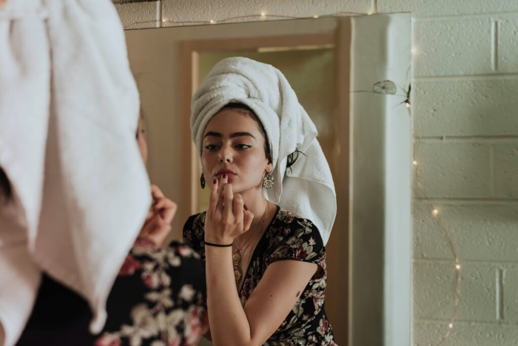 Personal Grooming Hacks Women with her hair up in a towel, looking into a mirror and applying product to her lips