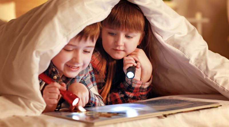 Makes It Simple for Kids to Love Reading / Boy and Girl under Blanket Reading with Flashlights
