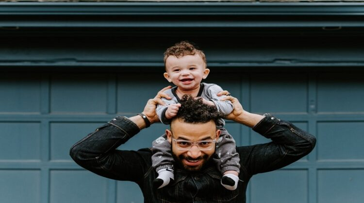 Dad holding toddler on his shoulders
